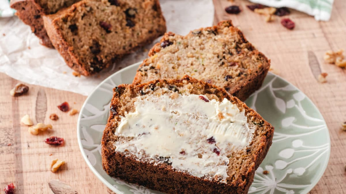 Delictable cranberry walnut zucchini bread topped with creamy butter