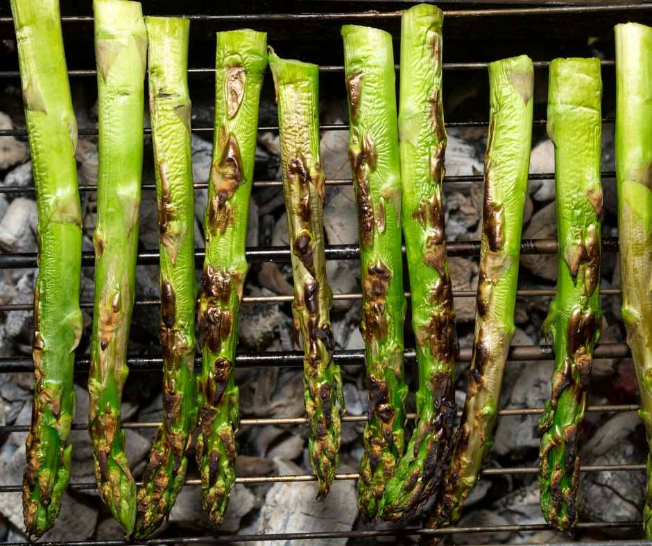 asparagus grilling over coal grill